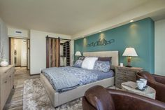 From the watery blue accent wall to the closet door crafted from reclaimed barn wood, it's the details that make the master bedroom of this oceanfront condo as picturesque as its view. Layered bedding adds richness and elegance to the space, while a shag rug provides softness underfoot.