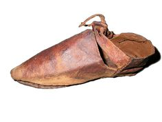 Child's shoe. It has a latchet fastening (a leather strap split into two at the end, which goes through a pair of holes). The wear on this shoe shows that the child who wore them was 'pigeon toed' - they walked with their feet pointing inwards. This distorted the shoe so much that it split and had to be re-stitched back together. Medieval shoes were made by 'cordwainers' (the word comes from 'cordwain', or 'cordovan', the name for the leather made in Córdoba, Spain). Late Medieval; late 14th