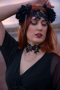 Elegant flower crown made of black roses on the sides of the head and a beautiful black lace piece lining the forehead. Three strands of silver tone chain decorate each side of the head. It is adjustable in the back with black ribbons. This is simple and elegant, fit for any occasion.