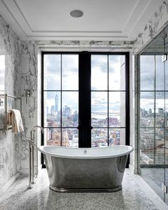 Unbelievable view of Manhattan from this marble bathroom with a silver free standing tub - Steele San Diego Homes @ SteeleSanDiegoHomes.com  #luxury #bathroom #marble #dreamhome
