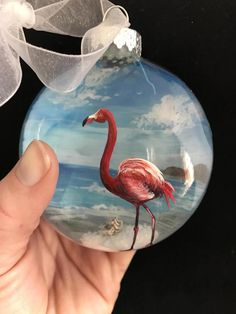 Pink Flamingo Hand Painted Glass Ornament Beach Nautical Tropical Ocean Paradise Christmas Tree Decor Sand Conch Shell Aqua Deep Blue Sea Feel a tropical Christmas coming on with this hot pink Flamingo hand painted glass ornament! The aqua blue ocean behind this brightly colored bird is a great way to make a pop on your beach themed tree. This one will definitely have you thinking, Is it a Christmas ornament or is it just something pretty I want to display all year long? Well, its both! The…