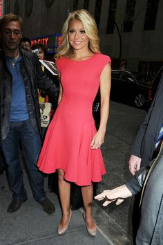 Kelly Ripa in a coral sheath dress with a full skirt and padded shoulders.