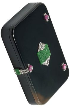 Art Deco Black Agate, Platinum, Carved Jade and Ruby Bead and Diamond Box, Cartier, France  18 kt., the rectangular black agate box with rounded corners, centering one rectangular carved jade plaque approximately 18.4 x 13.3 mm., flanked by two rose-cut diamond-set plaques, accented by 2 rectangular platinum plaques centering 2 diamond-set carved ruby beads flanked by 8 rose-cut diamonds, circa 1920.