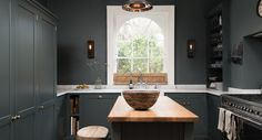 Copper ceiling lighting, rustic sconces, white marble counters and dark walls. Love the arch in that window.