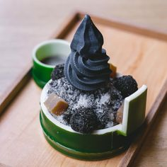 """""""Goma Kakigori."""" """"Kakigori,"""" or traditional Japanese summer shaved ice, topped with black sesame balls, home-made warabi mochi and a swirl of bamboo-charcoal soft serve. Served with a sweet black sesame sauce on the side."""