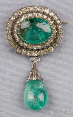 Antique Emerald and Diamond Pendant\/Brooch prong-set with a cabochon emerald measuring approx. 18.80 x 14.75 x 8.15 mm framed by old mine-cut diamonds and yellow diamonds approx. total diamond wt. 3.50 cts. suspending a detachable emerald drop measuring approx. 16.75 x 14.10 x 11.10 mm rose-cut diamond accents silver-topped gold mount.