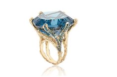 """Natalie Dissel's """"Ring Topaz King"""" offers a 115-carat London blue topaz with a concave cut, set in 18-karat yellow gold with blue diamonds."""