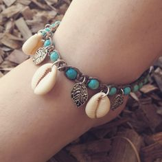 Adjustable Hand Weaved Turquoise Anklet from Khaki Hemp. It has Cowrie shells and Tibetan Silver Leaf Charms.
