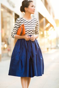 Silver and cream chevron sweater, full royal blue skirt, large orange clutch, poufed updo hairstyle
