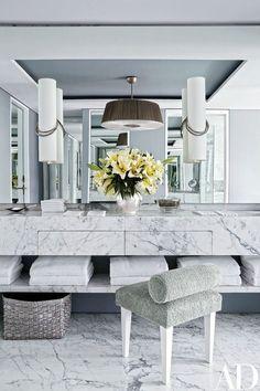 Hervé Van der Straeten sconces overlook the room's marble vanity; the stool is clad in a Perennials terry cloth | archdigest.com