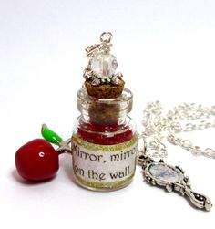 This beautiful Snow White inspired bottle charm necklace has an enamel Red apple charm and a glittering Silver plated mirror pendant. This