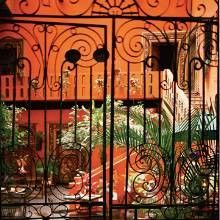 An elaborate set of wrought-iron gates opens to a vividly painted courtyard.