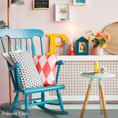 Der türkisfarbene Schaukelstuhl mit gemusterten Kissen ist der Mittelpunkt dieser Sitzecke. Boden, Wand und Couchtisch in Pastellfarben lassen den Raum feminin …
