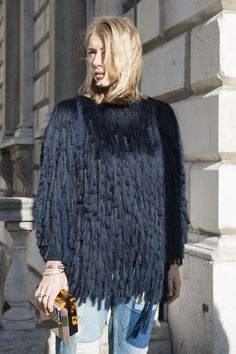 Fringe sweater, patchwork jeans, delicate bracelets and rings, and tortoise box clutch.