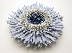 Israeli artist Zemer Peled creates sculptures using countless ceramic shards. Each individual element is a small part of a greater whole, and their sharp and pointed edges form a single beautiful form that's inspired by flowers or sea creatures. Through careful arrangement, these forms bloo