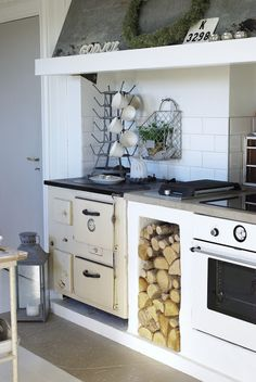 A vintage vibe in a modern kitchen. LOVE the Aga-like stove... and the wood stack.