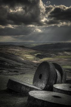 A group of millstones lie abandoned at the site where they were carved by hand from the hard Millstone Grit of the Peak District.  Crepuscular rays illuminate the old hill fort of Carl Wark and Hathersage Moor while a curtain of rain can be seen falling on Totley Moor in the far distance.