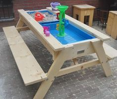 Sand and Water Picnic Table Make sand and water play simple, with a picnic table DIY project. The picnic table has benches your kids can sit on while they play.