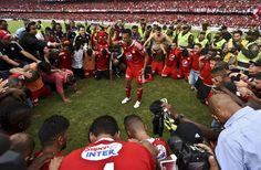 America de Cali's team players pray after defeating Deportes Quindio in a Colombian Professional Football tournament promotion match in Cali, Colombia, on November 27, 2016. America de Cali defeated Deportes Quindio by 2-1 and returned to first division after five years. / AFP / LUIS ROBAYO