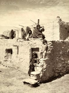 Hopi Indian children in front of an adobe styled building