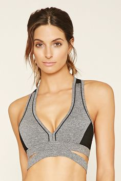 A high impact sports bra crafted from heathered knit with removable cups, a mesh-paneled design, contrast piping trim, a cutout back, a deep V-neckline, and cutout sides.
