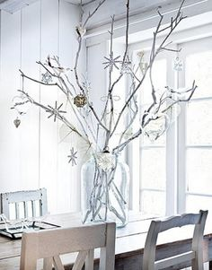 Simple, decorated branches, in a large glass vessel.