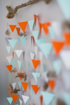 Detail of our DIY sewn paper triangle and feather garland wall hanging from our woodland adventure themed nursery in grey, white, orange, and mint.