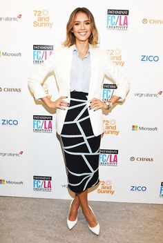 Jessica Alba is wearing a blue button-up tucked into a black midi pencil skirt, paired with a white blazer and pointed toe heels.