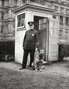 """April 12, 1929. """"King Tut, President Hoover's big German police dog, now makes the rounds of the sentry boxes in the White House grounds through the night. He is shown with W.S. Newton of the White House police."""""""