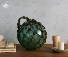 Eloquence, Inc. Antique Glass Buoy Fantastically cool antique glass buoy from France. In old deep aqua glass, softened and weathered by the sea. The old knotted hemp rope netting is stained gray and green from exposure and moss. I would put a few together in an antique French Tian Pot.