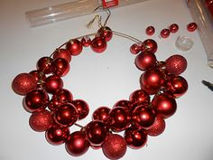 Wire Hanger Wreath Tutorial.  You string ornaments on wire rather than hot gluing which seems much easier!