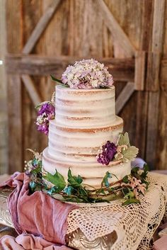 semi-naked wedding cake with purple hydrangea accents
