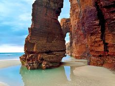 """Why we love it: A small stretch of sand on the Galician coast where natural stone arches form a walkable """"cathedral"""" at low tide."""