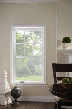 Single-hung window with grids increase natural lighting through a beautiful frame. Pair white trim with light wall paint to make the room appear bigger.