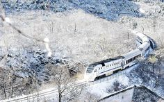 A train travels through hills covered by snow after heavy snowfall on the outskirts of Beijing, China