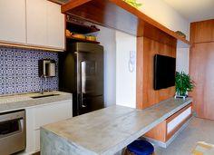 Painel de correr para TV permite integrar ou isolar a cozinha do primeiro apê do casal