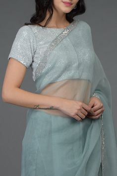From our sheer glamour collection, this is an aqua grey pure organza silk saree adorned with sequin beads hand embroidered borders. Paired with an aqua grey fine net blouse adorned with stunning hand embroidered sequin and beads all over. Saree Blouse Neck Designs, Saree Blouse Patterns, Saree Blouse Models, Skirt Patterns, Coat Patterns, Sewing Patterns, Drape Sarees, Organza Saree, Indian Dresses