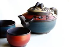 """Wonderfully colorful Tea Set! Three color teapot (blue, red and creamy yellow) with brown flower and leaf accents and two matching 3 ounce tea bowls - one red and one blue.  Bamboo branch handle lid and spout styling. Just the thing to enjoy tea time with someone special. Fitted with stainless steel infuser basket.  Teapot 17.5 oz capacity. 7 3/4"""" wide (handle to spout) x 4"""" high."""