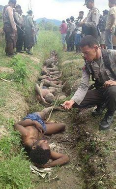 This is what they are doing to the West Papuan people . Slaughtering them in cold blood while the world looks on. This photo of an Indonesian pig taking a photo on his mobile phone sickens me to the core.