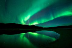 Aurora Borealis -  Dramatic display is reflected in water Ifjord in Finnmark, Norway