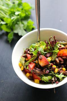 Syvän etelän papusalaatti  noin 3 annosta  Pavut:      1 prk kidneypapuja     1 prk mustapapuja     2 pienehköä kesäsipulia (säilytä varret)     3 valkosipulinkynttä     1 rkl rypsiöljyä     2 tl savupaprikajauhetta     1,5 tl juustokuminaa     2 tl vaahtera- tai agavesiirappia     yrttisuolaa ja mustapippuria     chilijauhetta maun mukaan  Salaatti:      erilaisia lehtisalaatteja     0,5 ruukku tuoretta korianteria     100 g kirsikkatomaatteja     2 persikkaa     2 sipulin varret     1…