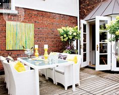 Bright contemporary deck Nothing makes an outdoor space feel more like home than luxe accessories and artwork. Made for dining and entertaining, this outdoor retreat is centered around a large canvas painting hung on the aged brick wall, decorative candleholders and comfortable armchairs for all.