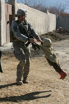 "A US Soldier playing ""helicopter"" with a local boy."