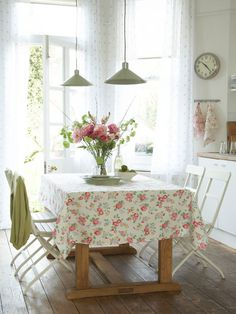 Even if you don't have a garden, you can still have flowers at home with a pretty floral tablecloth.  The scale is perfect for this eclectic, compact kitchen.