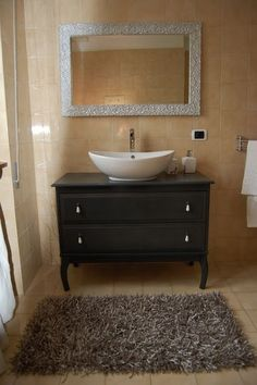 Go with a simple black vanity but add a vessel sink to add character.