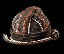 Fang helmet hat - men and women in this region had rich hairdos in helmet shape, decorated with beads, cowries, buttons, and brass nails and constructed over raffia or palm leaf supports. Some hats were fashioned in the same manner and form. According to Tessmann, the hats were made only by the Fang and the Ntum. The hats, like the coiffures, were worn daily, but the hats were removed for hunting and mourning.  D: 23 cm; H: 18 cm, coll. in situ, about 1960