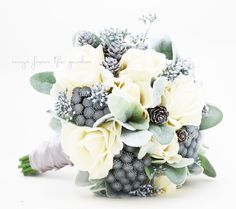 For your winter wedding, this elegant bouquet of roses, brunia, seeded eucalyptus, lamb's ear and pine cones can be yours to have and to hold on your day in the spotlight. We can work together to crea