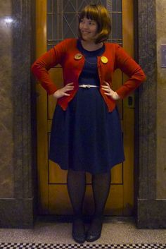 This chick knows how to do the dress, the tights, the little cardie. And the two broaches on either side. Love.