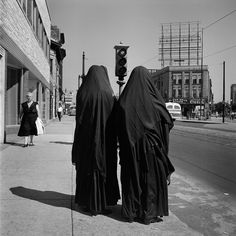 Two nuns seen from the back on a city sidewalk with a traffic-light poised behind them  VM19XXW00602-04-MC