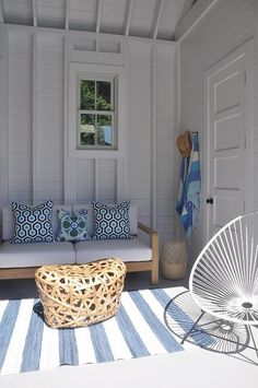 A teak sofa topped with white cushions complemented with aqua and navy geometric pillows and a white wicker chair sit around a woven coffee table placed on a blue striped rug in a blue and white cottage style pool house.